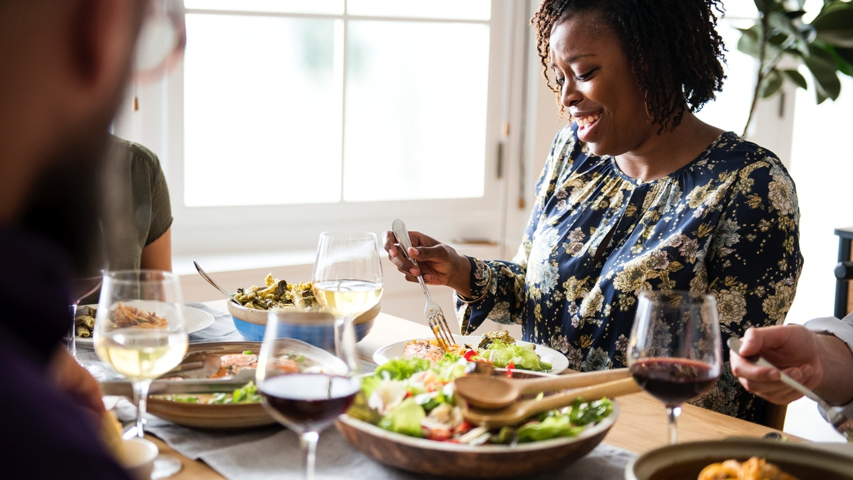 people sitting around a dinner table with the a large salad serving bowl at the center of the table and the focus being on one woman on the right who is picking up food with a fork